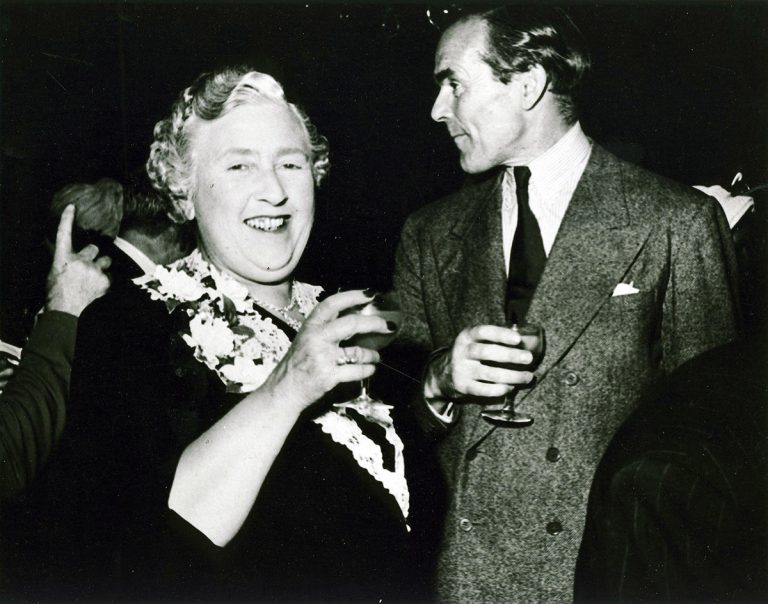Agatha Christie and Collins enjoying a drink at a party.
